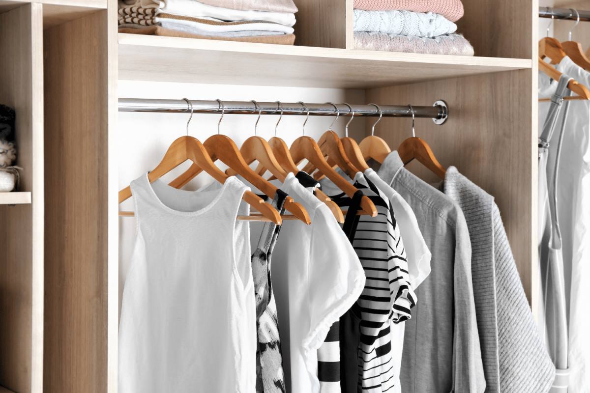 closets with wooden hangers and clothes hanging - best hangers for closet organization