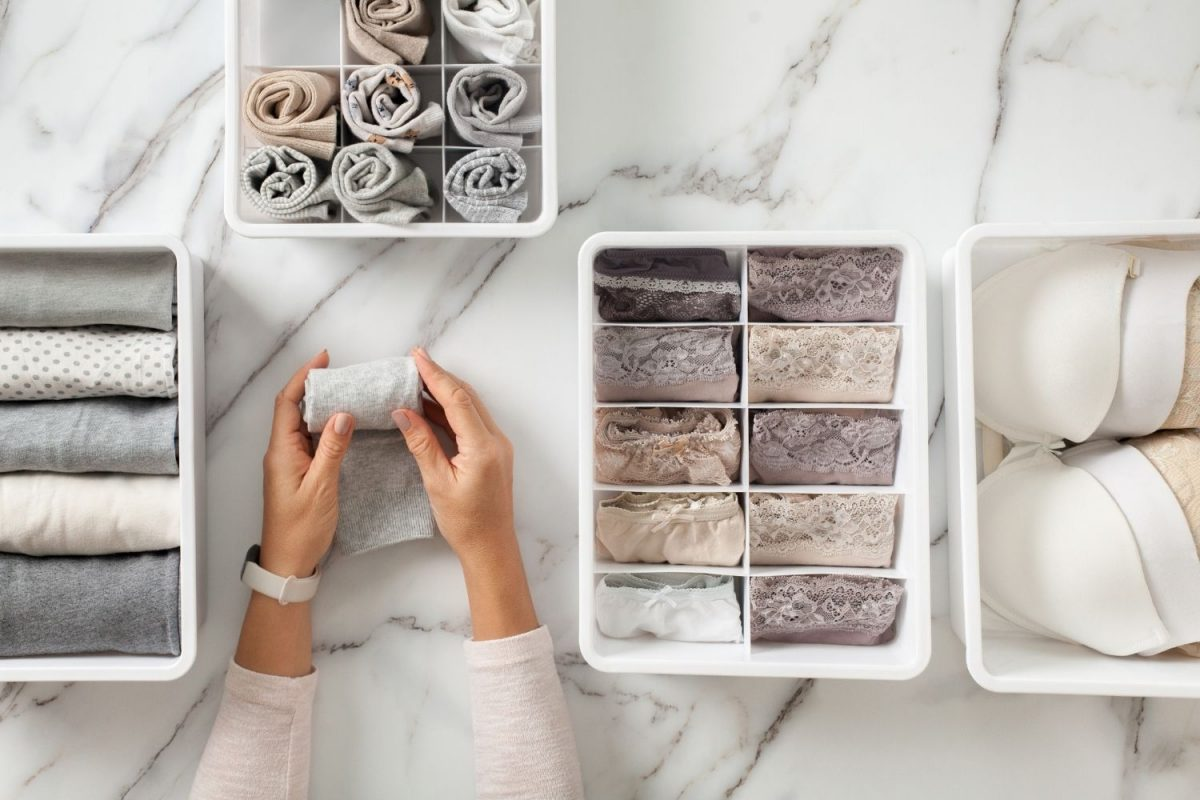 hand folding clothes in best organizing containers become a professional organizer